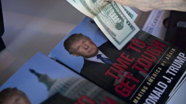 A guest pays for books near a book by Donald Trump at the summit in Ames, Iowa, on Saturday.
