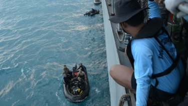 Grim search: Indonesian navy divers prepare operation to lift the tail of the AirAsia plane.