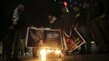 Palestinians burn posters of the Donald Trump during a protest in Bethlehem.