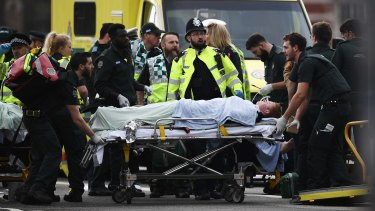 A member of the public is treated by emergency services near Westminster Bridge after the attack.