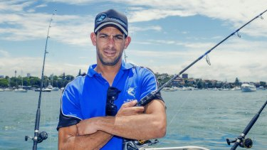 Adam Cree checks the FishBrain app before he heads out on Sydney Harbour.