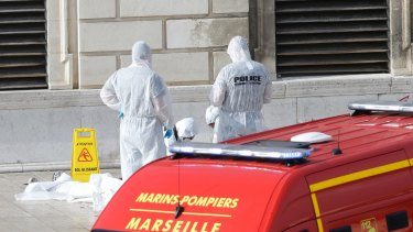 Investigative police officers outside Marseille 's main train station on Sunday after aA man with a knife attacked people at the station.