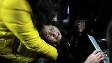 A woman grieves at a hospital where those injured by a stampede are being treated in Shanghai.
