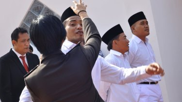 Mahendra, son of Bali Bomber Amrozi, centre, before raising the Indonesian flag on Independence Day 2017.