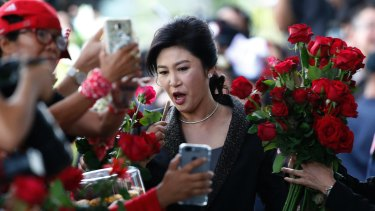 Thailand's former Prime Minister Yingluck Shinawatra receives roses from supporters as she arrives at the Supreme Court to make her final statements in a trial on a charge of criminal negligence in Bangkok on Tuesday.