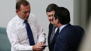 The ties that bind: Tony Abbott (left) examines the label on the tie of fellow conservative MP Michael Sukkar as Kevin Andrews looks on.