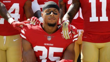 San Francisco 49ers' Eric Reid kneels in front of teammates during the playing of the national anthem.