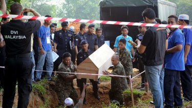Malaysian police carry a coffin containing the remains of a Rohingya migrant in 2015. Mass graves were also discovered in southern Thailand.