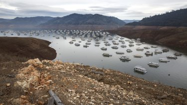 Houseboats at Bidwell Canyon Marina drop with the water level in Lake Oroville, California.