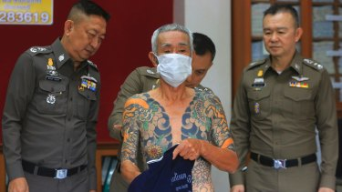 Japanese gang member Shigeharu Shirai displays his tattoos at a police station in Thailand.