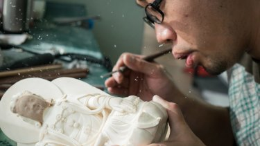Ivory dust flies as Zhang Yong blows it away during carving at Li Chunke's ivory carving workshop in Beijing on Monday.