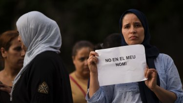 """A woman in Ripoll holds a placard stating in Catalan """"not in my name""""."""