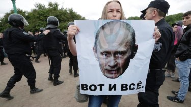 A woman holds a poster depicting Russian President Vladimir Putin with the slogan 'This is it' during an anti-corruption rally in St Petersburg on June 12.