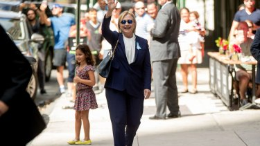 Hillary Clinton waves after leaving her daughter's apartment on Sunday.