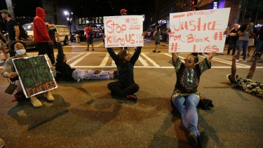 Demonstrators sit on a street during a protest in Charlotte.