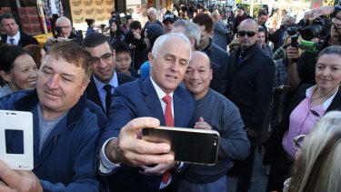 Mr Turnbull takes one of many selfies at Hurstville station in Sydney on Wednesday.