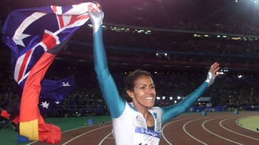 Cathy Freeman carries both the Aboriginal and the Australian flags during a victory lap after winning the women's 400m final at the Sydney Olympics in 2000.