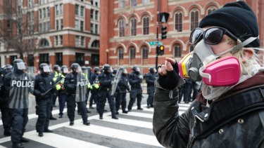 A protester faces off with a line of riot police in Washington, DC, during the inauguration.