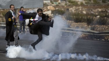 A Palestinian lawyer wearing his official robes kicks a tear gas canister back toward Israeli soldiers during a demonstration near Ramallah in the Israeli-occupied West Bank.