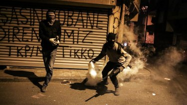 A masked and armed Kurdish protester throws back a teargas canister as they clash with Turkish police in Gazi district, in Istanbul.