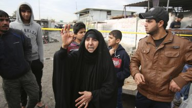 An Iraqi woman and others at the scene of the market bombing in Baghdad on Monday.