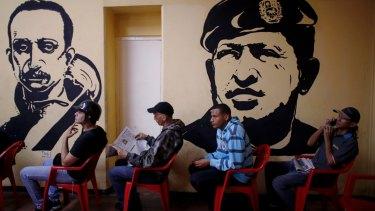 Voters wait to cast their ballots next murals of Venezuelan independence hero Ezequiel Zamora, left, and late Venezuelan President Hugo Chavez at a polling station in Caracas, Venezuela.