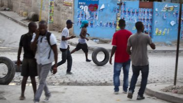 Supporters of presidential candidate Moise Jean-Charles gather tyres to be burnt in protests against poll results.
