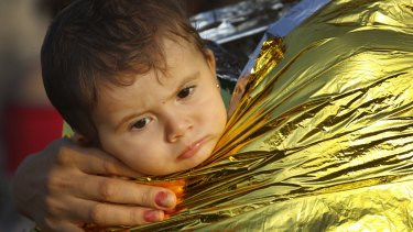 A Syrian refugee child is covered by thermal blanket in Kos following a rescue mission on Monday.