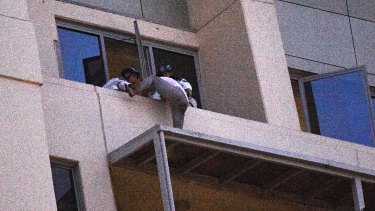 A man who spent the day on an awning on a high rise building in Chatswood gives himself up to Police Rescue members.