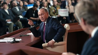 Russian President Vladimir Putin points to reporters during his annual news conference in Moscow.
