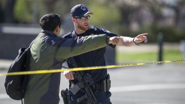 A US Capitol police officer directs a pedestrian to a detour after shots were fired at the visitor's centre of the Capitol building in Washington.