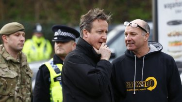 British Prime Minister David Cameron, centre, sent hundreds more troops into northern England on Sunday to help exhausted residents and emergency workers fight rising river waters.