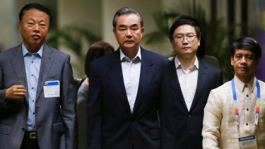 Chinese Foreign Minister Wang Yi, centre, is escorted by Chinese Ambassador to the Philippines Zhao Jianhua, left, on at the ASEAN meeting on Saturday.