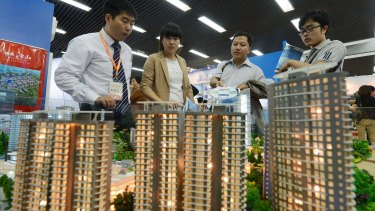 People view a model of a property development in Beijing.