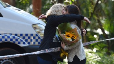 A woman with flowers embraces Faye Leveson (left), Matthew Leveson's mother, on Friday.