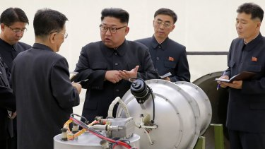 North Korean leader Kim Jong-un at an undisclosed location examines an explosive device.