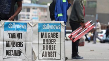 People pass a newsstand in Harare.