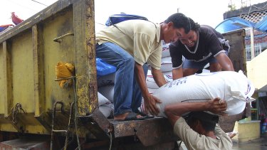 Workers unload sacks of rice intended for typhoon evacuees in Legazpi city, central Philippines.