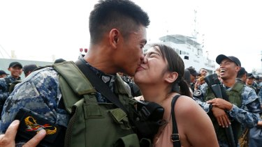 Philippine Coast Guard SN2 Dan Mark Torres  kisses his girlfriend Denise Guttierez, as his group are given a heroes' welcome with flowers and promotion in Manila.