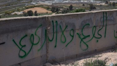 "Graffiti in Arabic reads ""hunger and not kneeling"", on a wall overlooking Israel's Ofer prison in the occupied West Bank."