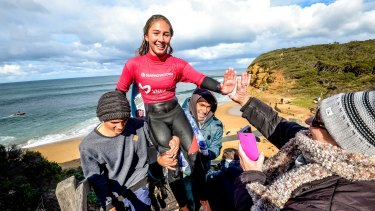 Summer being carried by her friend, Zac (left) and dad, Mark after winning the Women's Open title at the Australian Indigenous Surfing Titles at Bells Beach.
