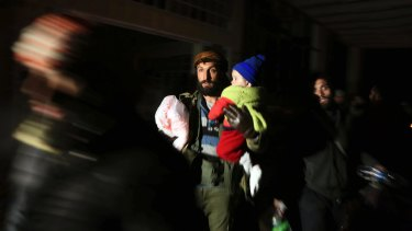 A man and child are evacuated as the UN voted to send monitors into Aleppo.
