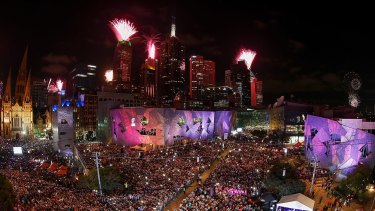 The midnight fireworks display, seen from Federation Square, lights up the city skyline during the New Year's Eve celebrations.