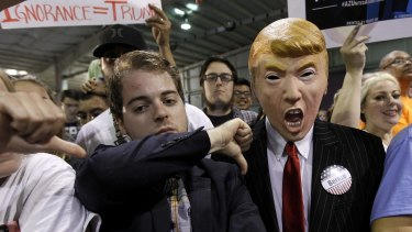 A supporter for Democratic presidential candidate Senator Bernie Sanders, gives the thumbs down sign to a fellow Sanders' supporter wearing a Donald Trump mask at a rally in Phoenix, Arizona, on Saturday.