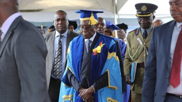 President Robert Mugabe, centre, leaves after presiding over a student graduation ceremony at Zimbabwe Open University on the outskirts of Harare on Friday.