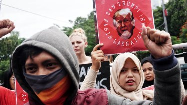 People hold placards during a protest against US President Donald Trump in front US Embassy in Jakarta in February.