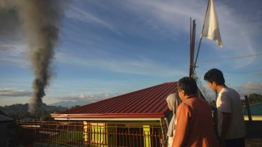 Marawi residents flying a white flag watch early morning air strikes by government forces.