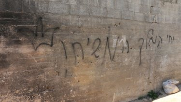 """Hebrew graffiti that reads """"long live the King Messiah"""", with a crown, sprayed on the wall of the Dawabshe family home."""