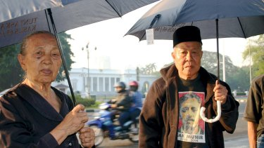 Sumini, left, and Anwar Umar, victims of the 1965-66 anti-communist crackdown, protesting outside the presidential palace in Jakarta.