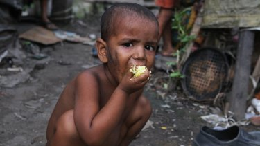 An Indian child eats rice at a slum area in Gauhati, India.